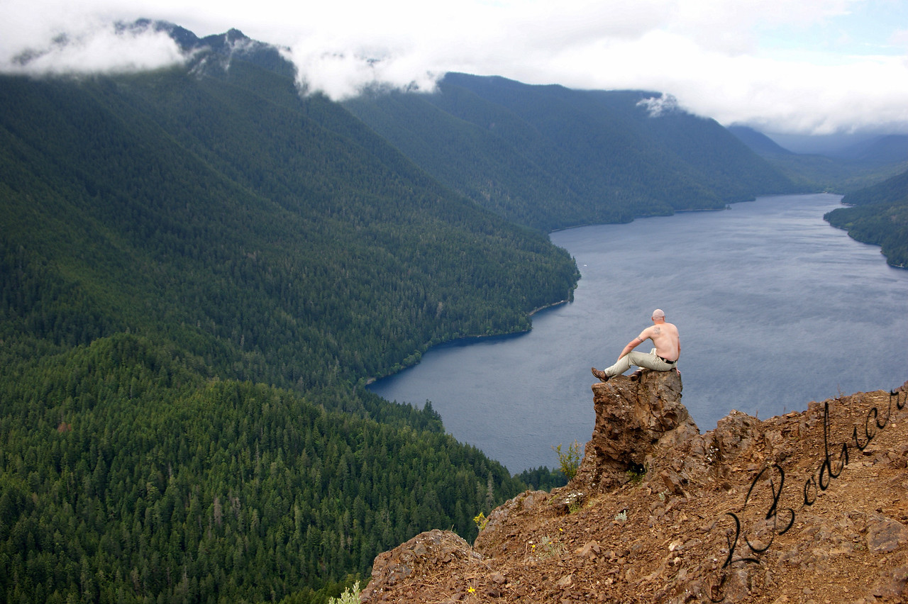 Photo By Bob Bodnar........................................Greg on the summit of Storm King Mountain<br /> Looking Down on Lake Crescent<br />  State: Washington<br />  Location: Olympic National Park<br />  Length, One-Way: 1.7 miles<br />  Trail Type: Out and Back<br />  Minimum Elevation: 700 feet<br />  Maximum Elevation: 2700 feet<br />  Elevation Change: 2000 feet<br />  Trail Surface: Maintained<br />  Best Season: Summer<br />  Difficulty: Difficult<br />  Usage: Heavy edit<br /> <br /> keywords: hike mountain · Edit