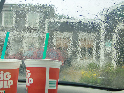 """Our 7-Eleven sodas on the dashboard of the car while we wait for the rain to let up. We are looking at the """"Shops of Rockaway"""" but more importantly, the public restroom."""