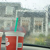 "Our 7-Eleven sodas on the dashboard of the car while we wait for the rain to let up. We are looking at the ""Shops of Rockaway"" but more importantly, the public restroom."