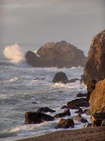 The rolling waves bounce against the rocks at the northern end of Rockaway Beach.