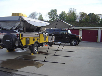 Lay each horizontal pole on the ground and move the vertical pole closer to the trailer so it support the awning.
