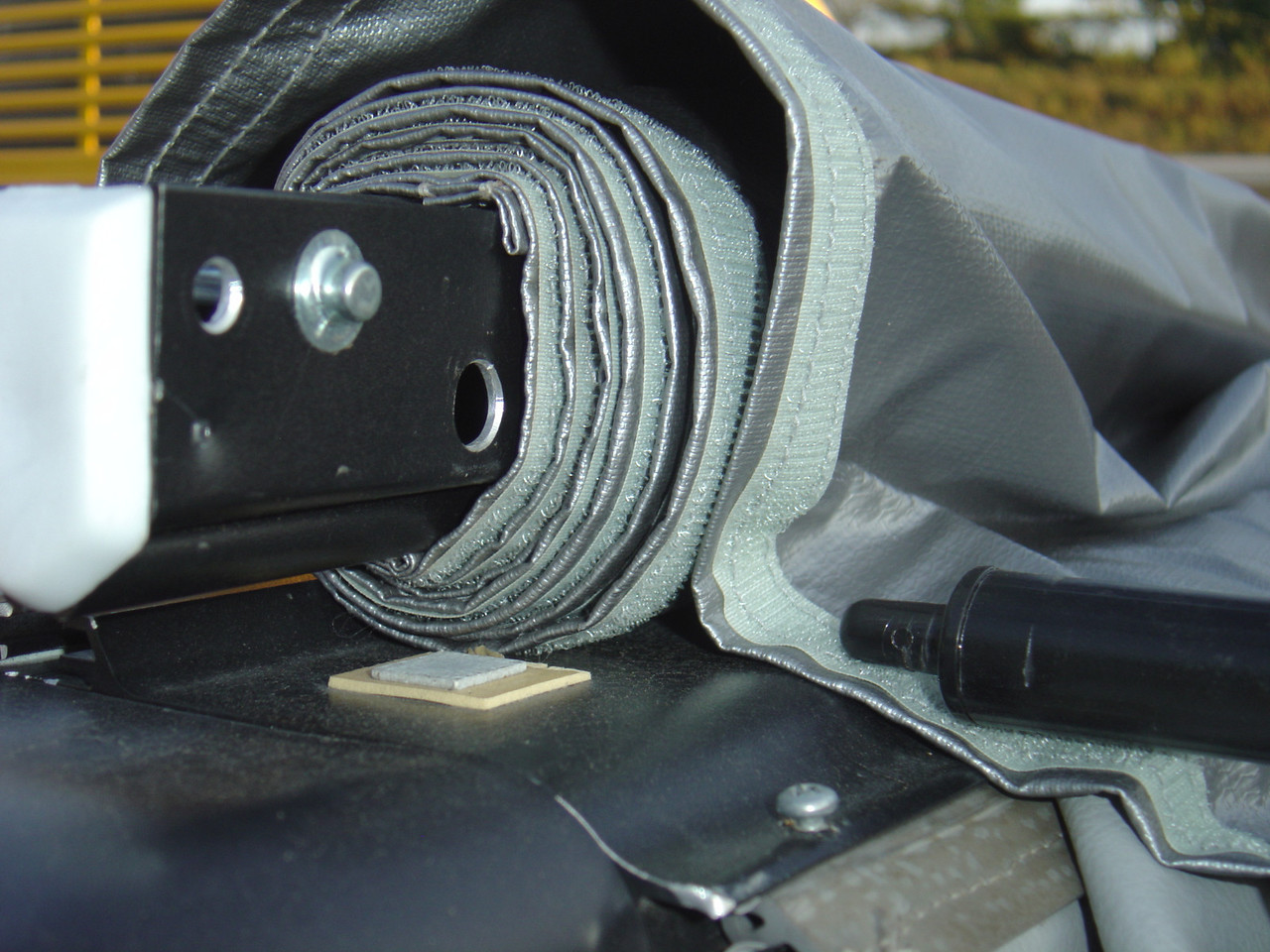 Roll up the awning.  Once you have it rolled up and into the bag you can move to the end of the bag and start zipping it close.(please ignore the awning pole in this photograph.  It was take to explain how the tip fits into channel.)