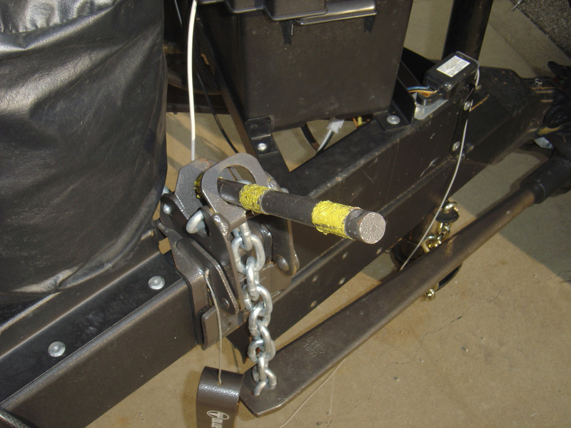 Insert the hitch release handle (rod with yellow tape) and move the tightener upward until it snaps in place