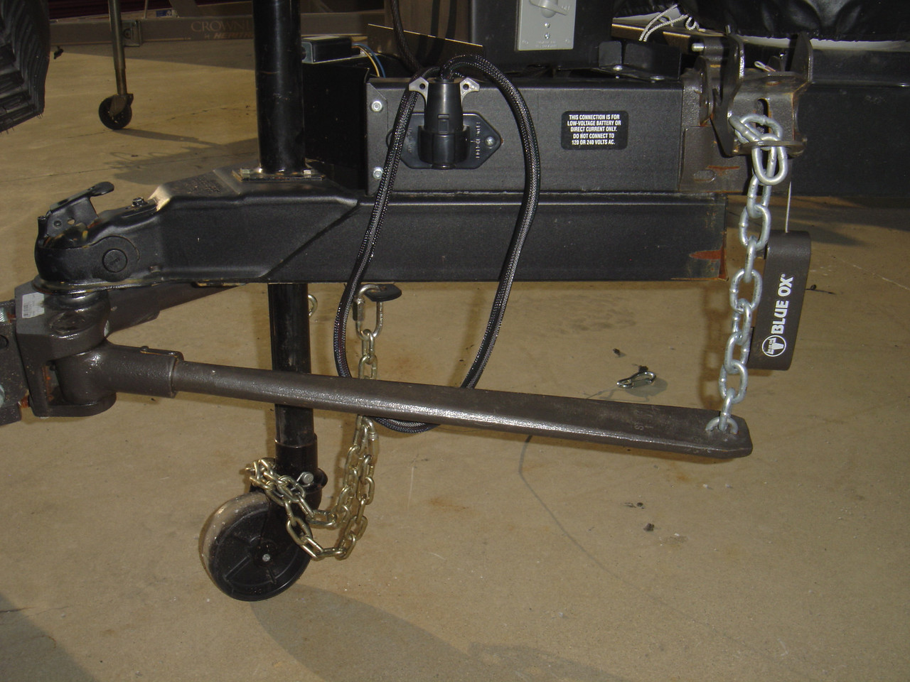 Raise the tongue to a high position. Slide the small end of the WDH bar with the sloted side up into the hitch head and slip the chain into the tightener bracket.  In my case there are 10 links of chain between the bar and the tightener bracket and this results in the bar being parellel with the ground with in tightener bracket is in place.