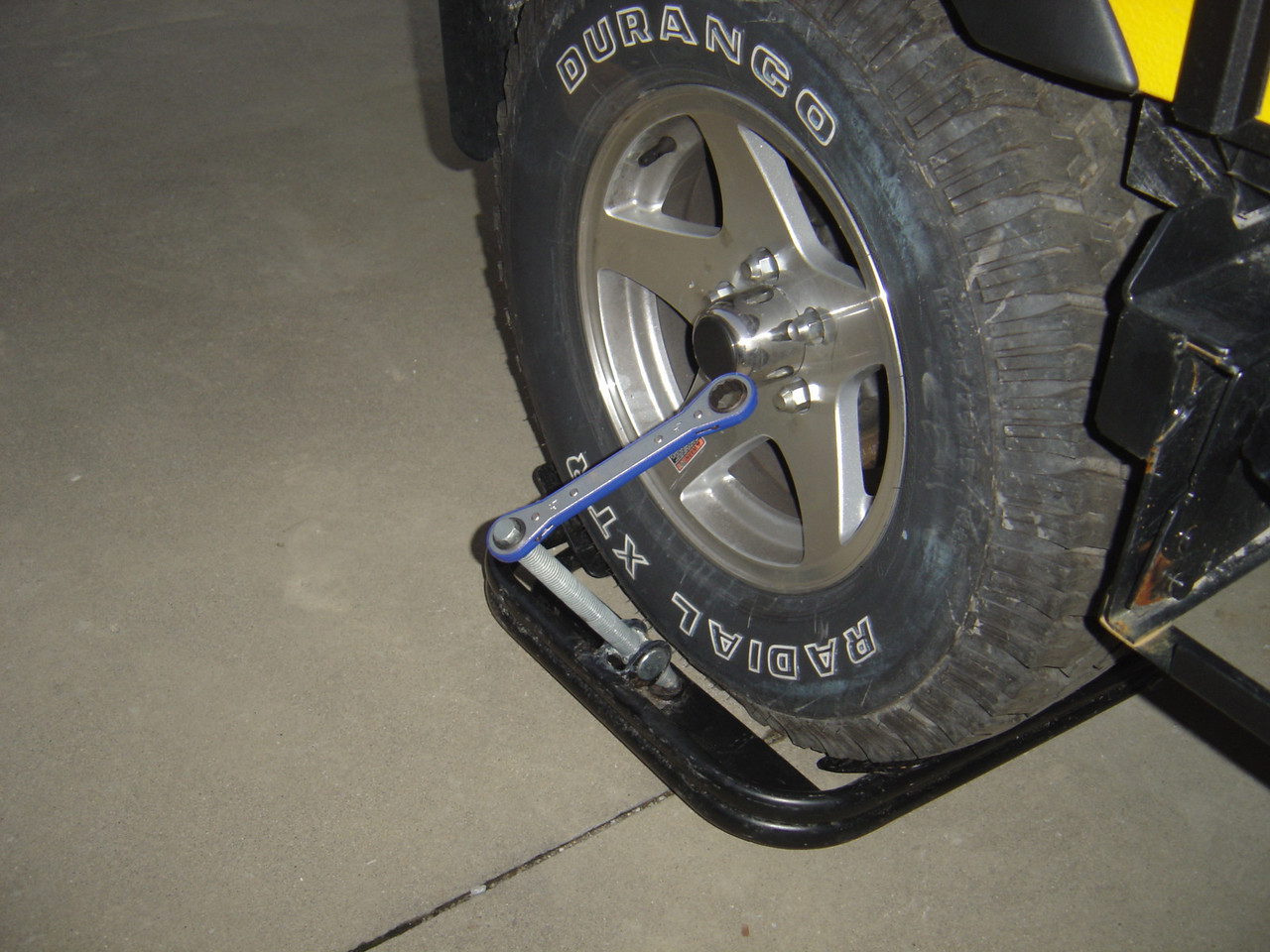 The BAL leverler is placed under the tire which needs to be raised.  The end of the screw needs to placed in a ring at the based of the leverler.  The wrench is turned clockwise to raise the tire and anti-clockwise to lower it.