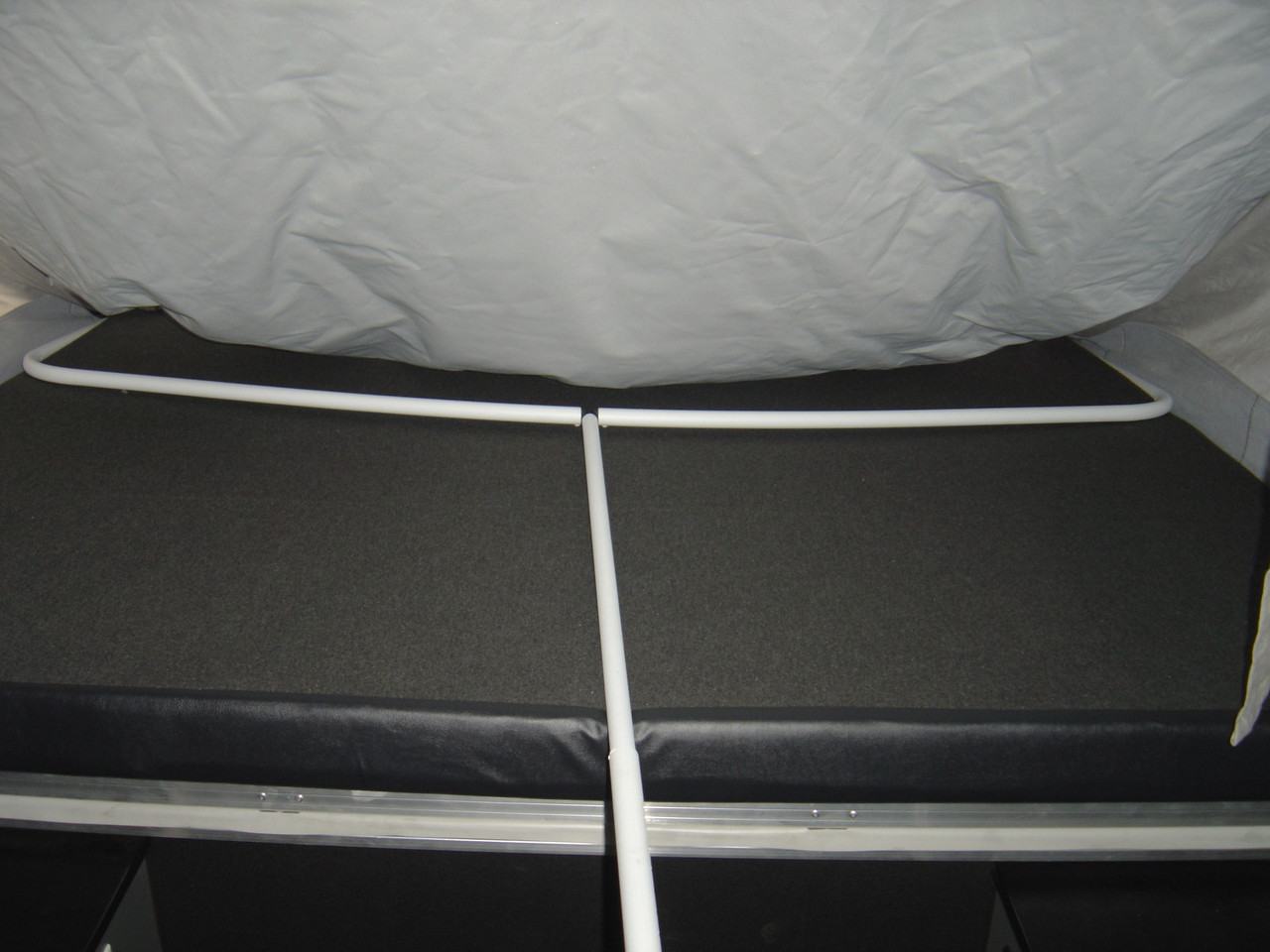 The support rod at the end of the tent will rest on the top of the mattress. The Shepherd pole goes under the mattress.