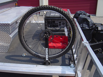 Front wheel in attachment.  Note that behind the wheel are four spring loaded hocks.  These are used to secure two gerry water cans.