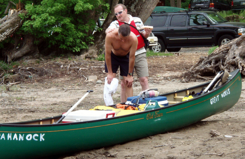Karl bends over his good ship Moxie at Ten Mile RIver, while his bowman Marc massages in the sunscreen.