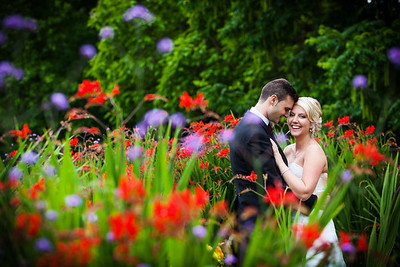 Colourful portrait of a bride and groom standing amongst flowers