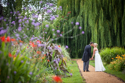Bride and groom walking through Beddington Park