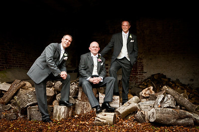 Groom and groomsmen sitting on chopped tree stumps