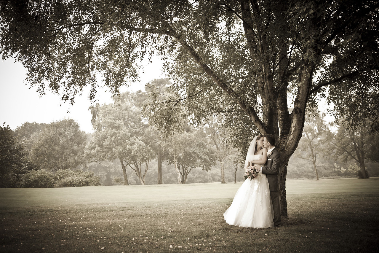 Intimate portrait of a bride and groom kissing under a tree at Kingswood Golf Club