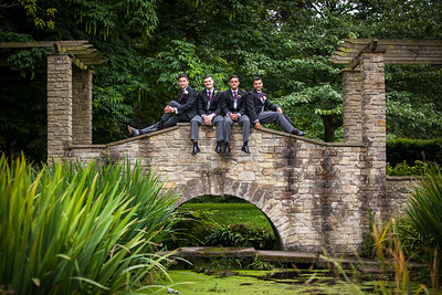 Groom and Groomsmen sitting on a bridge at The Grange in Beddington Park