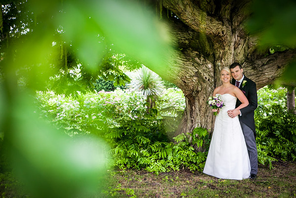 Bride and groom posing for a photo standing next a tree in Beddington Park