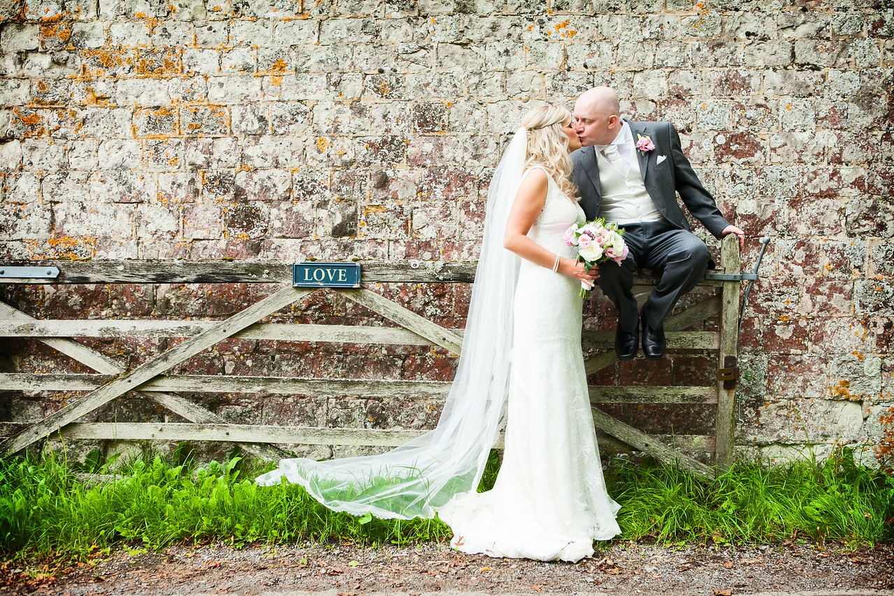 Groom sitting on a gate kissing his bride at Bury Court Barn