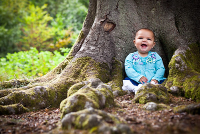 Baby girl portrait sat at the base of a tree
