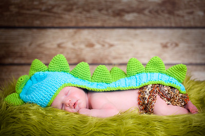 Newborn baby boy wearing a dinosaur woolly hat
