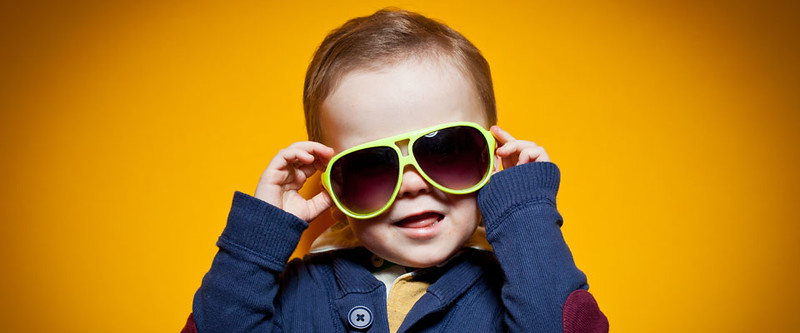 Young boy playing with sunglasses