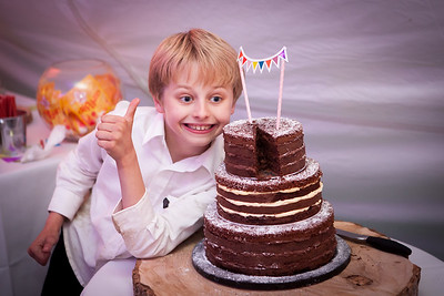 Young lad enjoys a picture next to the chocolate wedding cake
