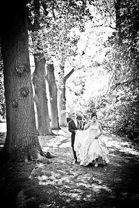 Groom assists his bride whilst walking through the grounds at Ghyll Manor