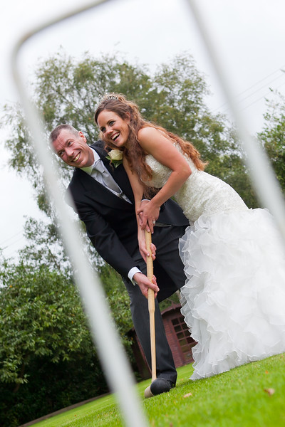 Bride and groom pose for a photo playing croquet