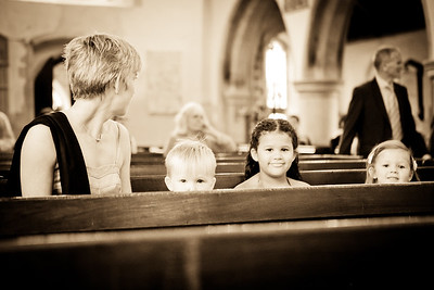 Three young children sitting in the church pews at St Michael's Church Betchworth