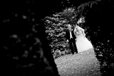 Bride and groom peeking through a gap in the hedge at Oaks Farm
