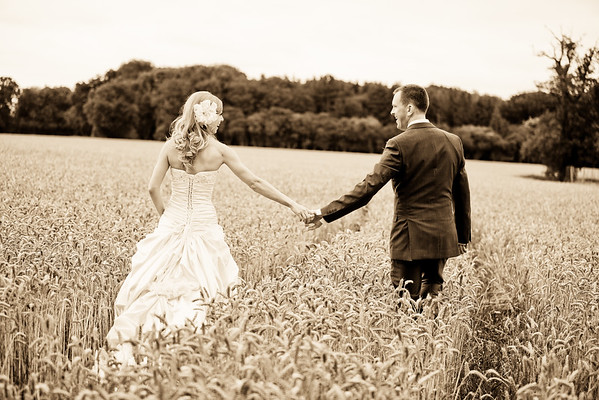 Bride and groom walking hand in hand in a wheat field