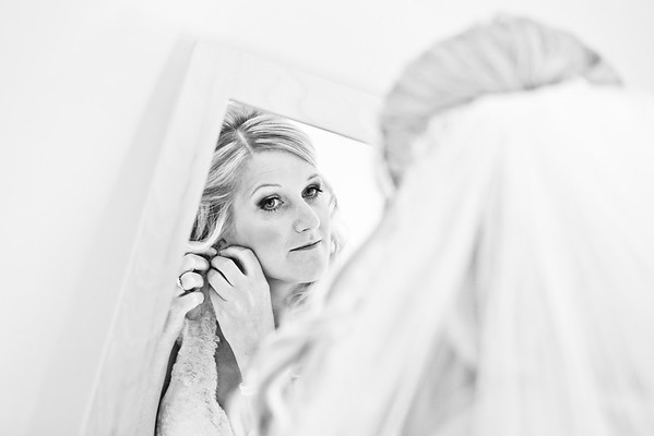 Bride adjusting her earrings in the mirror whilst getting ready for her wedding ceremony at Bury Court Barn