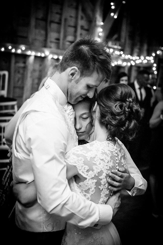 Groom, Bride and their son embrace during the first dance