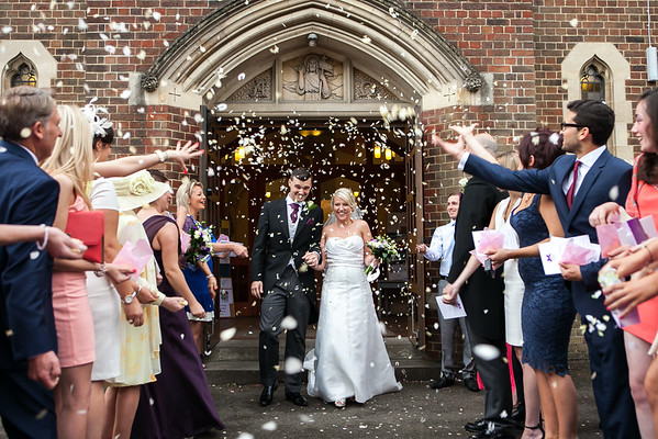 Bride and groom being showered in confetti at St John's The Baptist Church