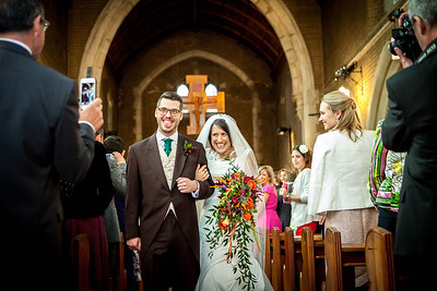 An overjoyed bride and groom walking back up the aisle at Holy Family Church in Reigate