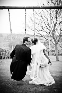 Bride and groom sitting on a swing having a kiss