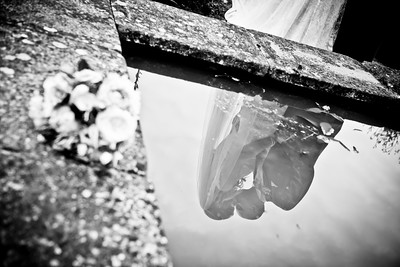 A reflection of a bride and groom kissing in a pond at Bury Court Barn