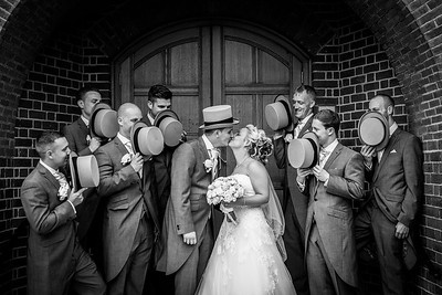 Bride and Groom kissing surrounded by their groomsmen