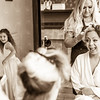 Bride smiles at cheeky bridesmaid whilst having her hair made up