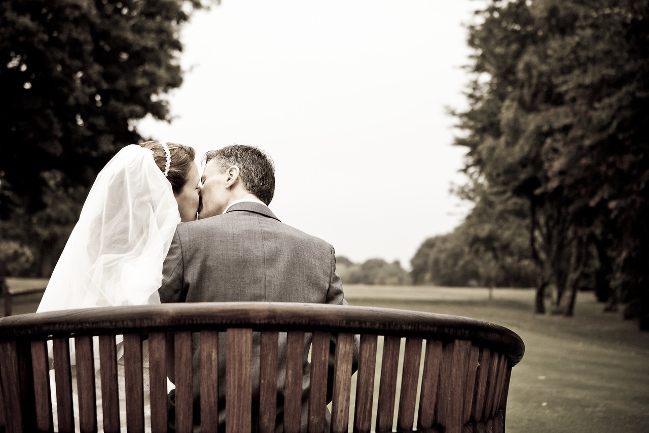 Bride and groom enjoy a kiss on a bench at Kingswood Golf Club in Surrey