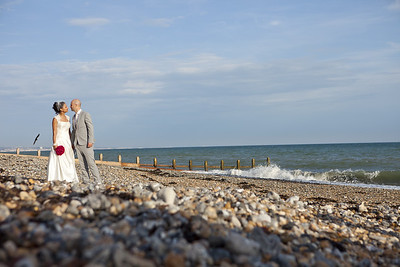 A bride and groom stopping for a kiss on Worthing beach in West Sussex