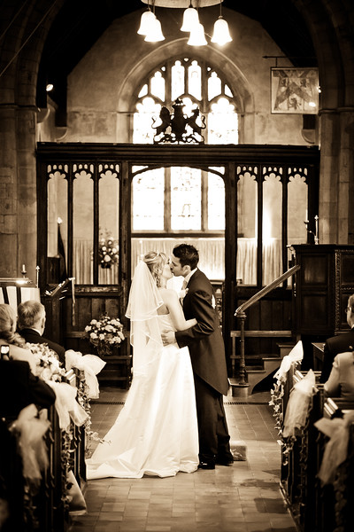 Bride and groom kissing at the altar at St Margaret's Church in Star Lane