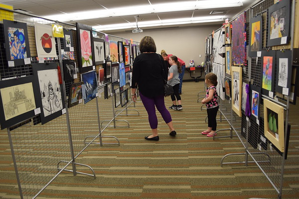 A family looks at several pieces of art work done by area students. Shown are Ty and Mandy Totten with their daughters, Mia, 7, and Madadalyn, 3, at the Children's Art Show, 2019. Dawn Schabbing photo