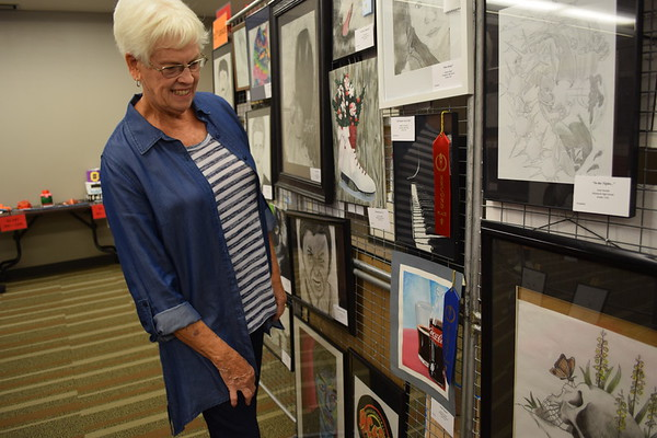 Karen Birch of Mattoon looks over her granddaughter's art displays. Camryn Crowell, a junior at Effingham High School, earned first place for 'Soda Poppin', an acrylic work. Dawn Schabbing photo