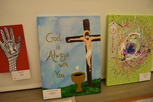 """Three works are: """"Spider Hand"""" by Issac Tays, third grade at Sacred Heart; """"God is Always with You,"""" by Cece Passalacqua, third grader at Sacred Heart; """"Fidget Spinner Art,"""" by Karly Zumwalt, third grader at Sacred Heart. Dawn Schabbing photo"""
