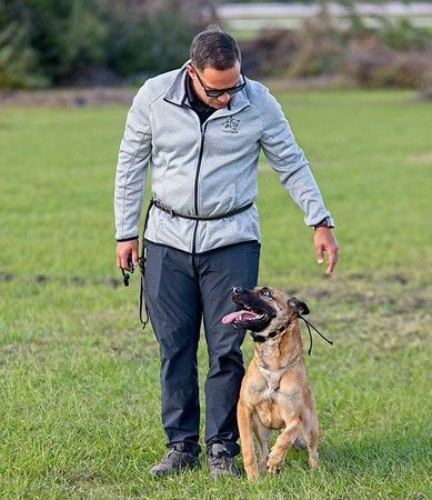 Hometown News - Coastline K9 - Erick Innis with one of his clients Roxy 2.5 yr old belgian malinois (PH1 with Honors) owner is John W. Smith Jr. in front of his porsch.