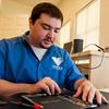iHeart Lead Tech Repairman Jason Fuchs working onn a broken iPad