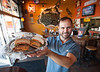 Matt Holt co-owner (along with his mother Pinki Goolsby and Shane Keinz burger creator/chef) holds one of his family's creations while standing in the Bradenton, Florida restaurant.  Photo by OdellPhotos.com on 12-18-2013