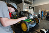 Small Engine Repairs - Thomas and Karen Niederer (owners) Brandon Hughes putting together the engine of a push mower