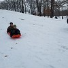 Will Bierman, 10, and Charlie Bierman, 8, glide down the hill at Community Park as two others hike back up, on Saturday. Dawn Schabbing photo