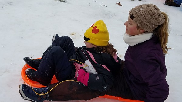 Josie Waymoth, 7, and Lilly Waymoth, 13, prepare to head down a hill on their sled on Saturday. Dawn Schabbing photo