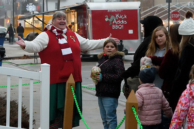 Patty Winn sings Christmas carols to the crowd waiting in line to see Santa during Hometown Christmas Saturday afternoon sponsored by the Downtown Effingham Business Group.  Chet Piotrowski Jr. photo/Piotrowski Studios