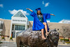 Graduating students pose for photos at the Bronze Buffalo on North Campus on May 16, 2020. Commencement ceremonies were presented virtually because of the COVID-19 response. <br /> <br /> Photographer: Douglas Levere